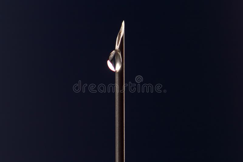 Macro photo of a medical needle for injection with a drop of liquid. The macro photo of a medical needle for injection with a drop of liquid royalty free stock images