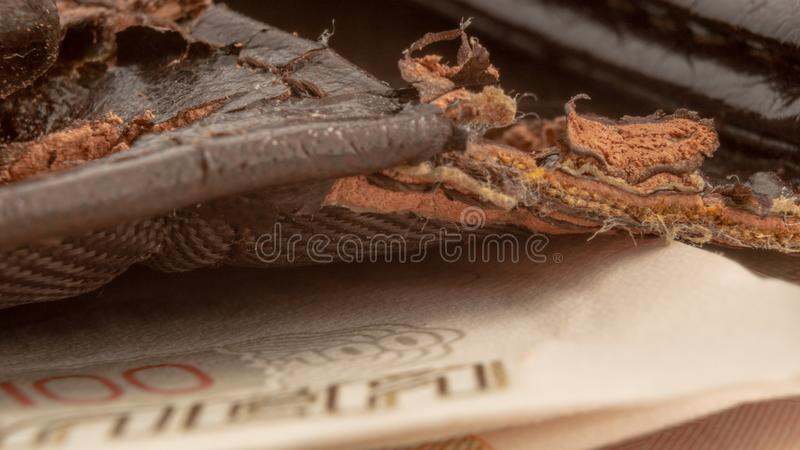 Macro photo of old torn brown wallet with money bills.  stock photo