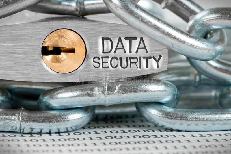 Padlock and Chains Concept. Macro photo of padlock and chains closeup with DATA SECURITY words imprinted on metal surface stock images