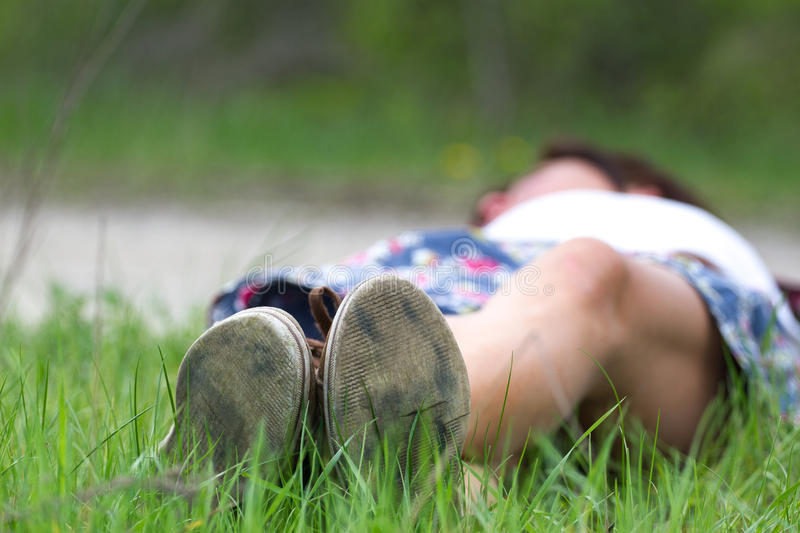Macro photo of shoe soles. Girl resting on grass after a long physical activity royalty free stock image