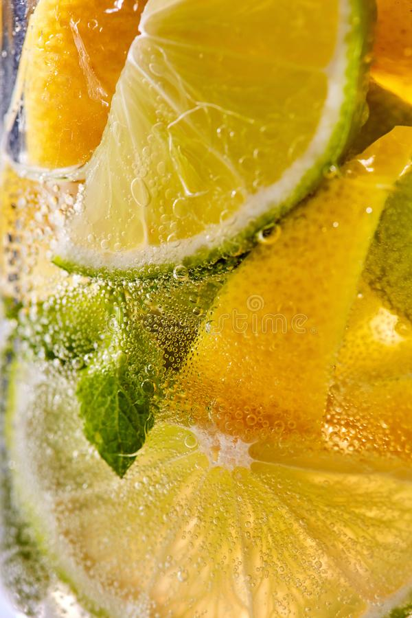 Macro photo of sliced lemon and lime with a leaf of mint and bubbles in glass. Cool drink mojito stock photography