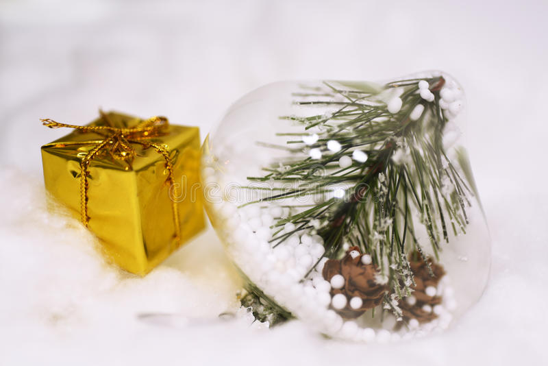 Macro photo of some Christmas objects. Yellow present with decorative cones in glass located on snow stock photo