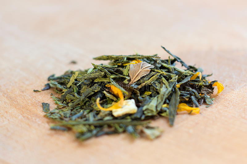 Macro photo of tea. The composition of the heap of dried hibiscus flower located on a wooden Board. Green natural tea with leaves stock image