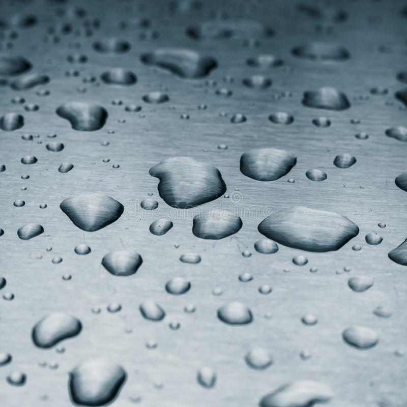 Rain drops on a brushed metal surface royalty free stock photography