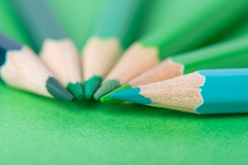 Macro photograph of several pencils of green color on a paper background royalty free stock image