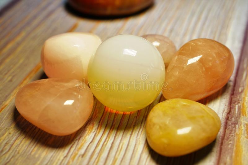 Macro photography of natural mineral from geological collection - polished yellow moonstone gem adularia on a wooden table. A stock photography