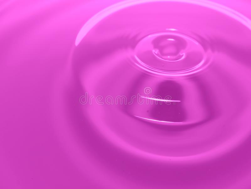Macro photography purple pink water drop / ink drops splash and ripples, wet, conceptual for environmental, conservation. stock photo
