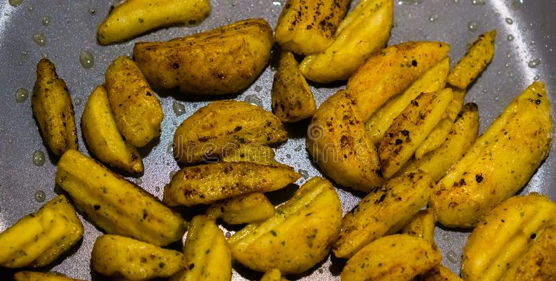 Macro plan rapproché des cales cuites au four d'or de pomme de terre dans une casserole, fond délicieux de nourriture de vegan photographie stock