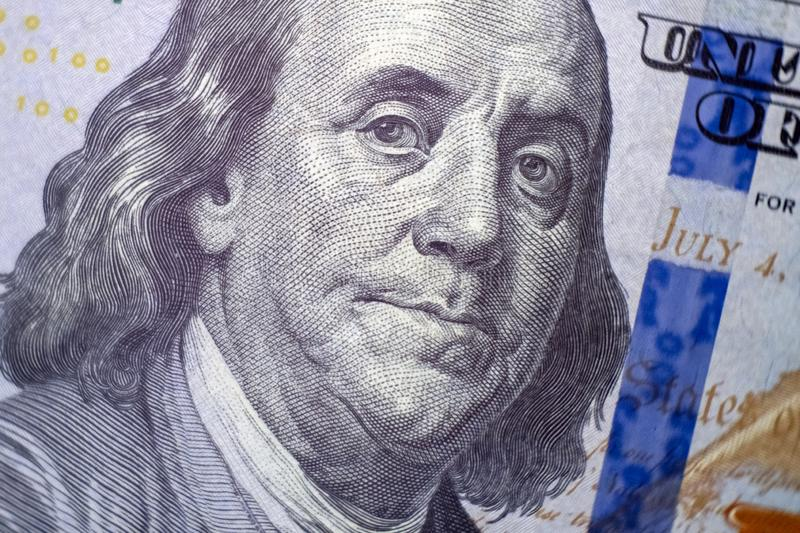 Macro. A portrait of Benjamin Franklin on a hundred dollar US bill. Blue protective strip. Close-up. Selective focus stock photo