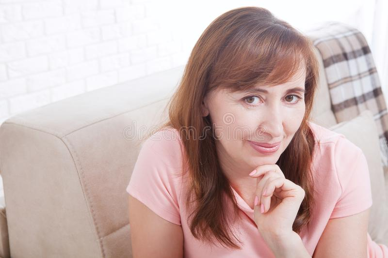 Macro portrait of smiling female face. Attractive and beautiful middle aged woman sitting on sofa and relaxing at home. Menopause. royalty free stock image