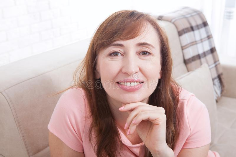 Macro portrait of smiling female face. Attractive and beautiful middle aged woman sitting on sofa and relaxing at home. Menopause. stock photo