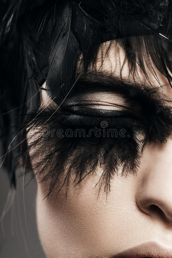 Macro portrait of woman eye with black feather royalty free stock images