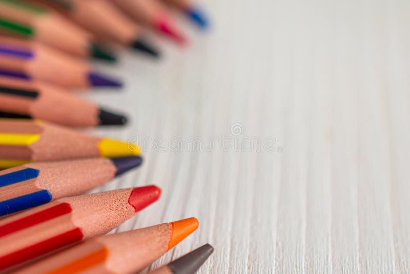 Macro primo piano messo a fuoco con fondo unfocused di parecchie matite colorate per scuola, nel semicerchio fotografia stock libera da diritti