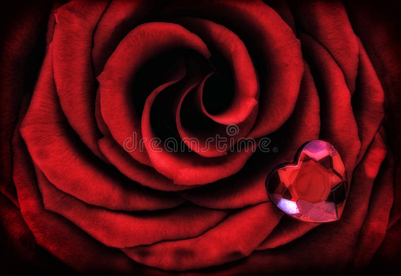 Macro Red Rose with Crystal Heart. A close up macro of a vibrant red rose with a small heart shaped crystal sitting on top of it stock image