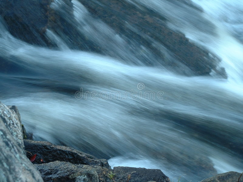 Macro of rocks by rushing water royalty free stock images