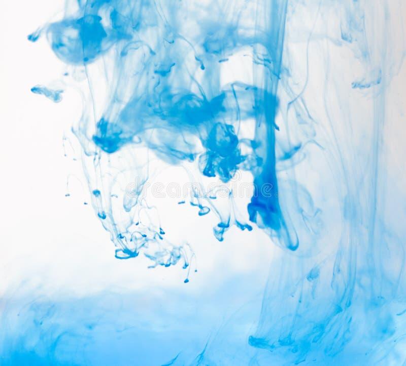 Macro, samenvatting De blauwe dalingen van de waterverfverf in water met witte achtergrond stock afbeelding