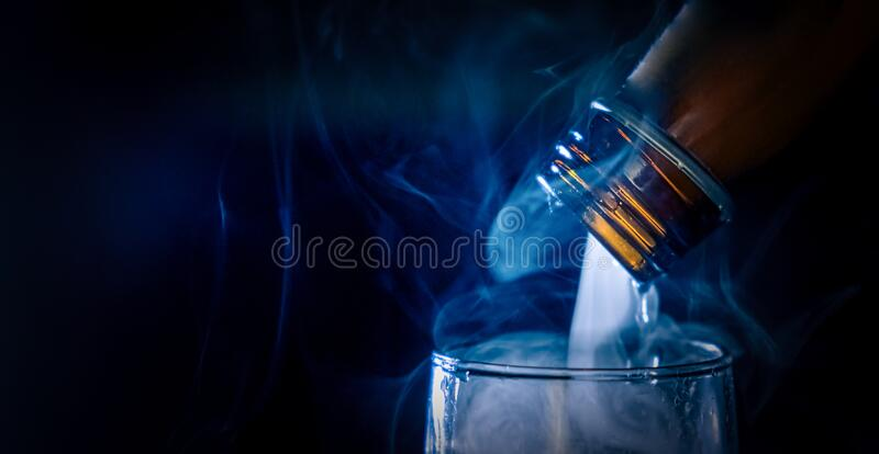 Macro shoot a bottle of liquor from which there is smoke or steam while the drink is being poured into the glass. Bad sinful stock images