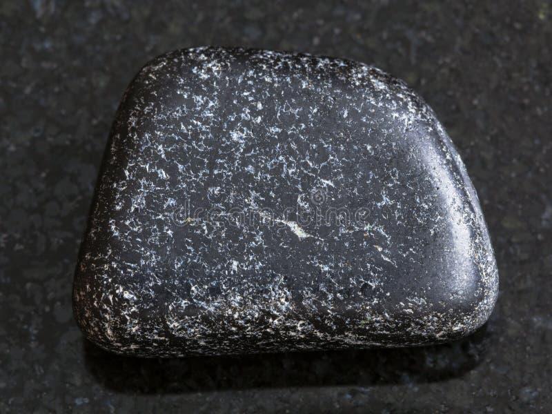 polished Chromite stone on dark background royalty free stock photo