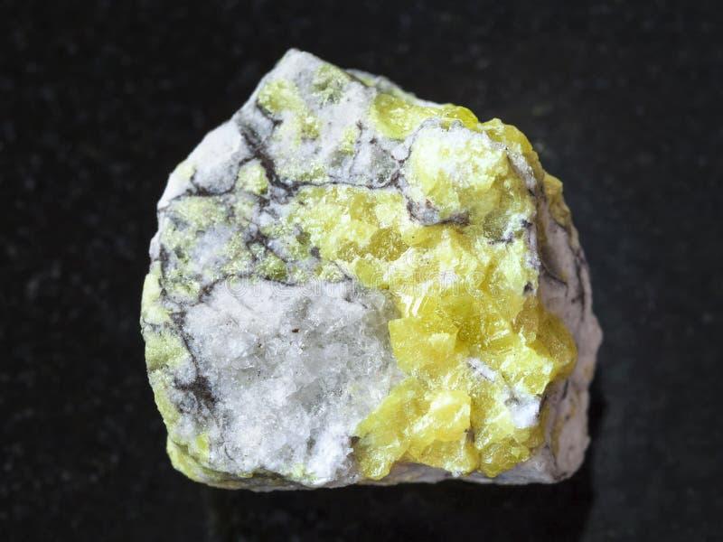 Raw sulfur ore on dark background. Macro shooting of natural mineral rock specimen - raw sulfur ore on dark granite background from Volodinskoye mine, Samara royalty free stock photography