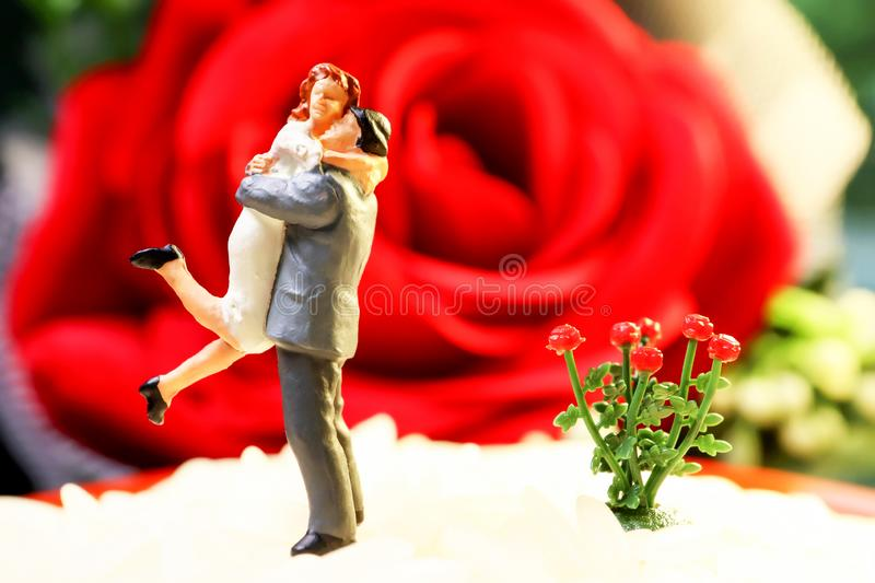 Macro shot of artifact tiny dolly lovers couples with flower red roses and background. Wedding and love concept.  royalty free stock images