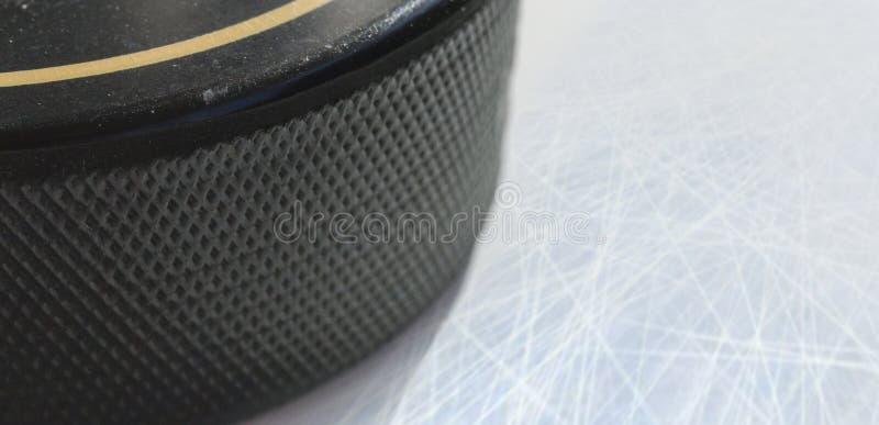 Macro shot of black hockey puck on ice rink royalty free stock photography