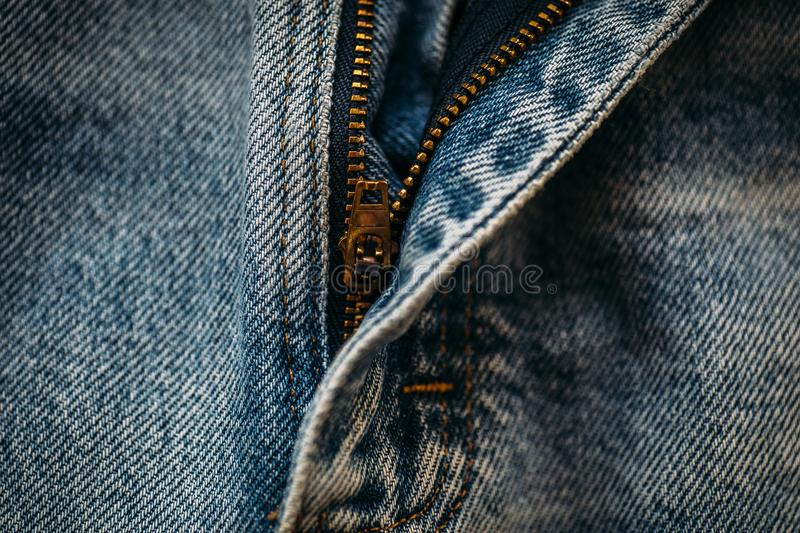 Macro shot of blue denim jeans with opened zipper. Toned stock photography