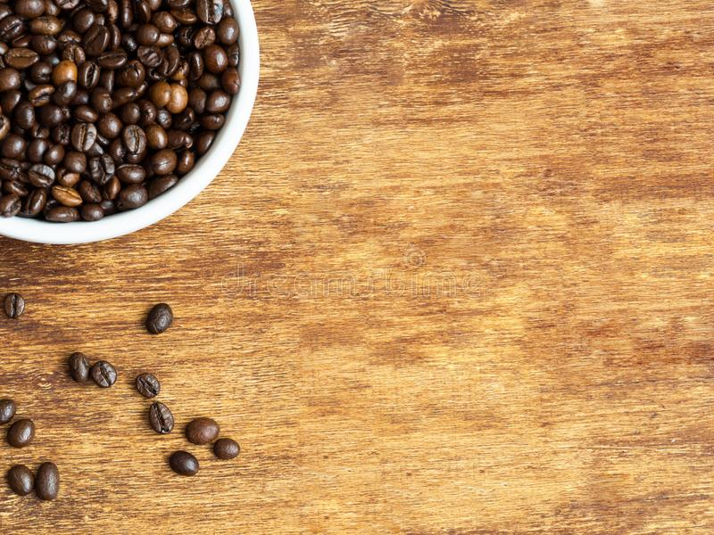 Macro shot of coffee beans in ceramic bowl and scattered coffee seeds on wooden background. Flat lay, copyspace royalty free stock photography
