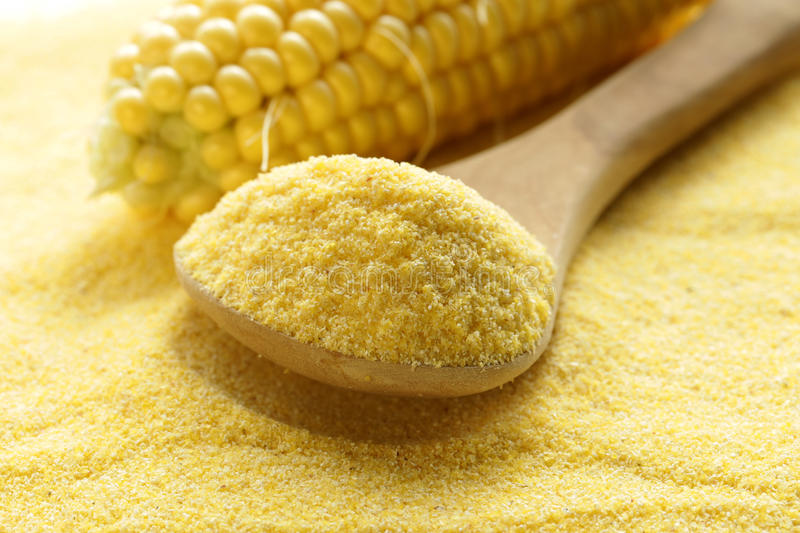 Macro shot corn flour in a wooden spoon royalty free stock photos
