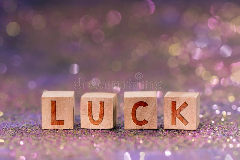 Luck word on wooden cubes. Macro shot of luck word written on wooden cube on color glitter with bokeh light royalty free stock image