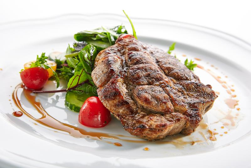Pork Neck Steak with Mixed Salad on White Restaurent Plate. Macro shot of pork neck steak with mixed salad on white restaurent plate isolated. Restaurant main stock photo