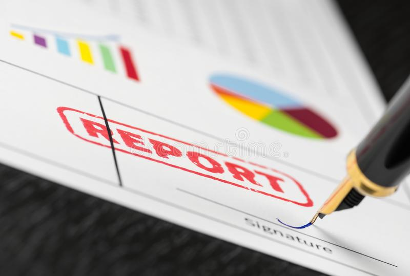 Macro shot of red stamp report and fountain pen on a form with colorful graphs. stock images