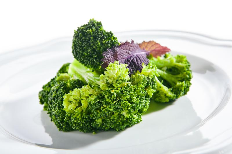 Macro Shot of Steamed Broccoli on White Restaurant Plate Isolated royalty free stock images