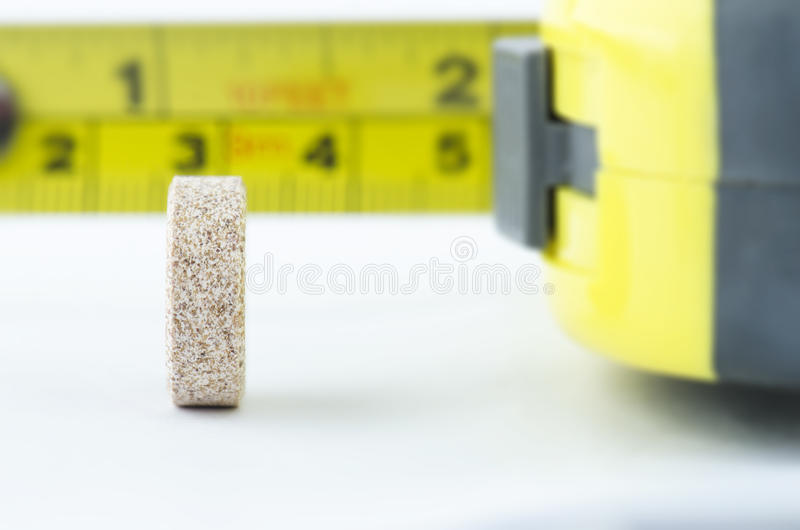 MACRO SHOT OF TABLET IN PROFILE WITH METER TAPE AT THE BACK royalty free stock images