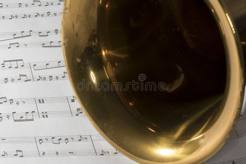Macro Shot of Tenor Saxophone on sheet music. Macro shot of Tenor Saxophone Bell on sheet music stock images
