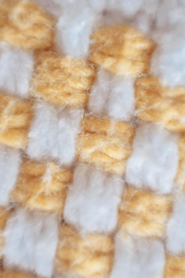 Macro of a woven piece of fabric. Macro shot of yellow and white threads of a woven piece of fabric royalty free stock images