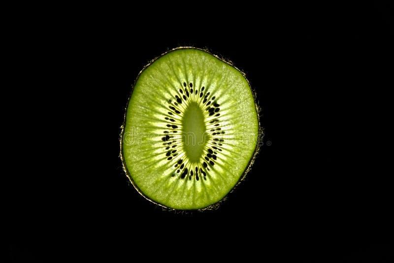 Macro of slim sliced kiwi fruit on black background stock photos
