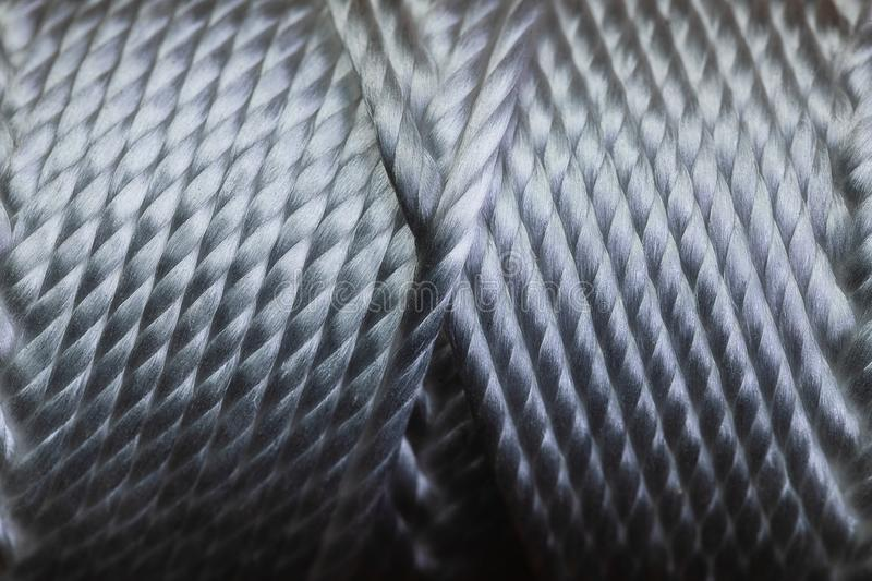 A macro of a spool of string wound in a very symmetrical pattern on a tube. The image is in very sharp focus and has a high. Contrast. The symmetry in the royalty free stock image