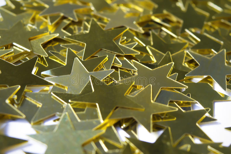 Macro of star-shaped golden sequins. Macro of star-shaped sequins in gold royalty free stock photos