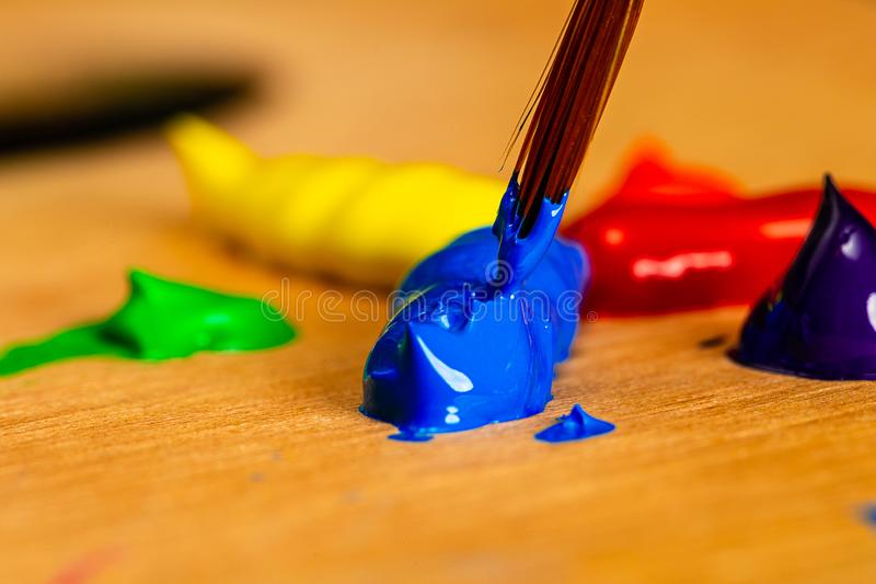 Macro tagliente del pennello di un artista che è caricato con la pittura acrilica blu dalle chiazze di pittura su una tavolozza i fotografia stock