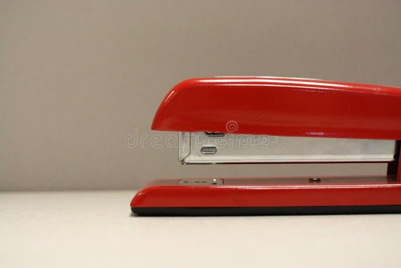Macro tir d'agrafeuse rouge dans un arrangement de bureau image stock