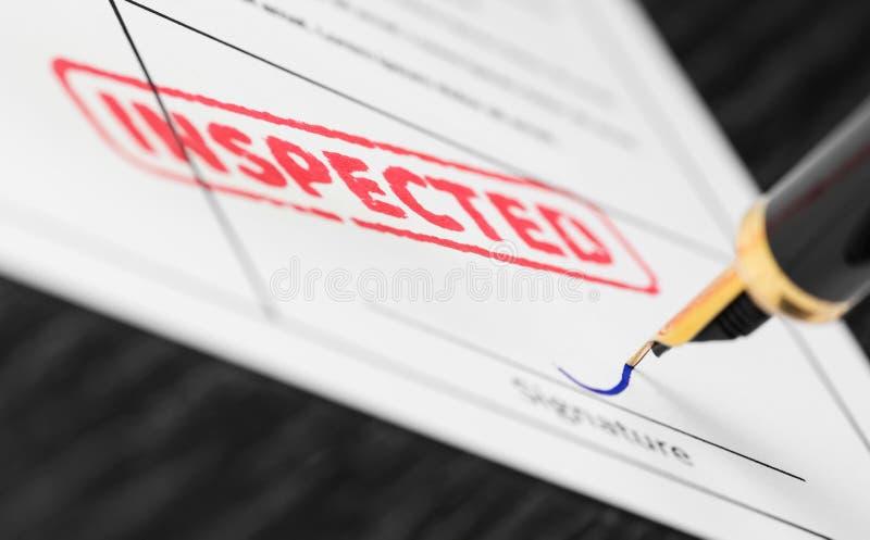 Macro tir de timbre rouge inspecté et de stylo-plume sur une forme photos stock