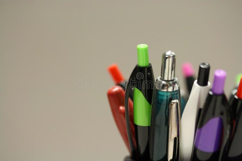 Macro tir des stylos et des crayons dans un arrangement de bureau photos stock