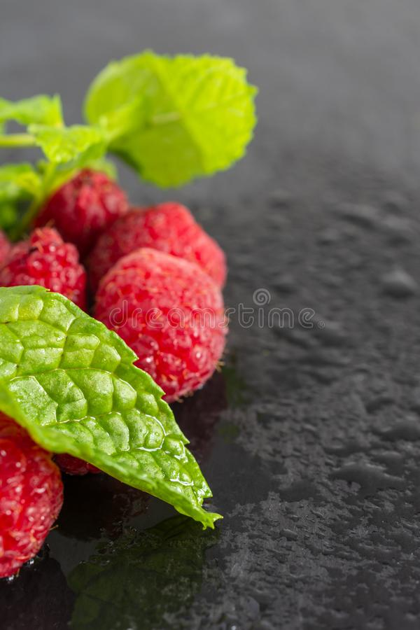 Macro top view of mint leaf and wet raspberries out of focus on black slate in vertical royalty free stock photography