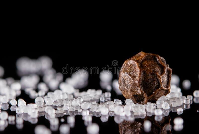 Macro van één enkele peperbollen en zoute kristallen op een zwarte achtergrond wordt geschoten die stock foto