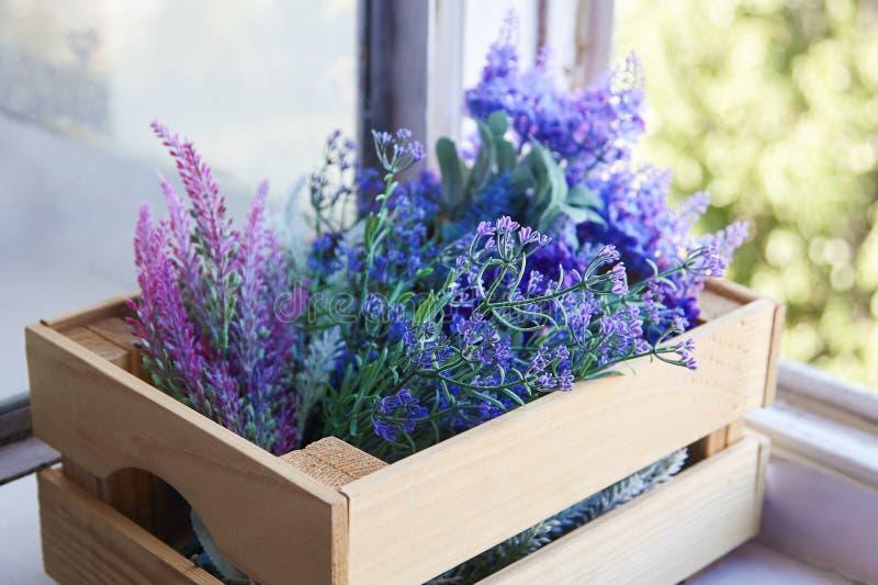 Macro van de lente lilac bloemen in houten kooi op de venstervensterbank, verschillende schaduwen van sering en viooltje stock foto's