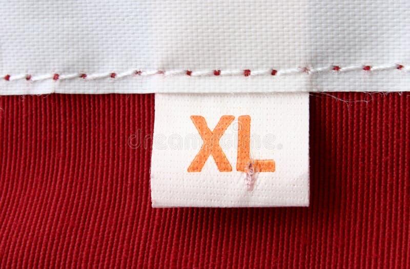 Macro verdadera de la escritura de la etiqueta de la ropa - CLASIFIQUE EL XL fotos de archivo libres de regalías
