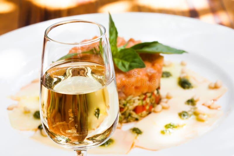 Macro vetro di vista di sherry jerez, fondo di color salmone rosa del piatto del tartaro del pesce, fuoco molle Scena di estate immagine stock libera da diritti