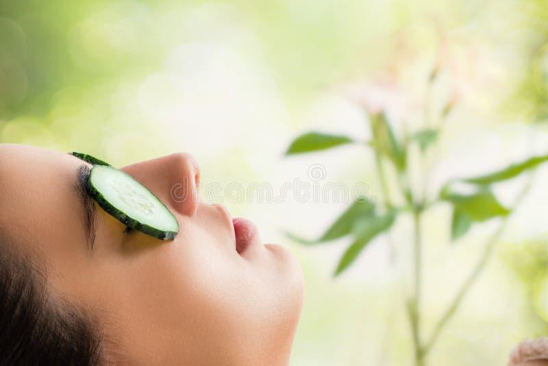 Macro vicina su delle fette d'uso del cetriolo della donna sugli occhi immagini stock