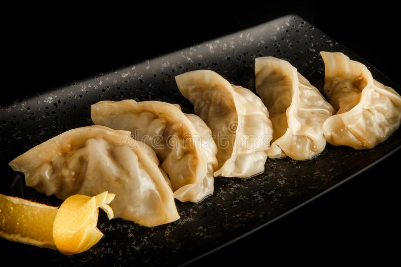 macro view asian gyoza dumplings with orange slice on plate stock image