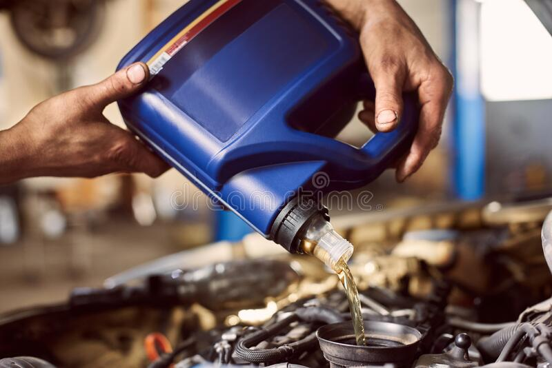 Macro view of blue bottle in dirty hands pouring oil into car engine. Replacing engine lubricants in auto service center. Macro view of blue bottle in dirty male stock images